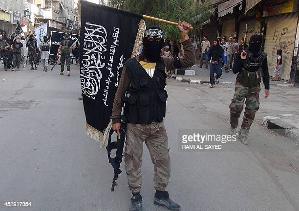 Islamic fighters from the alQaida group in the Levant AlNusra Front wave their movement's flag as they parade at the Yarmuk Palestinian refugee camp...