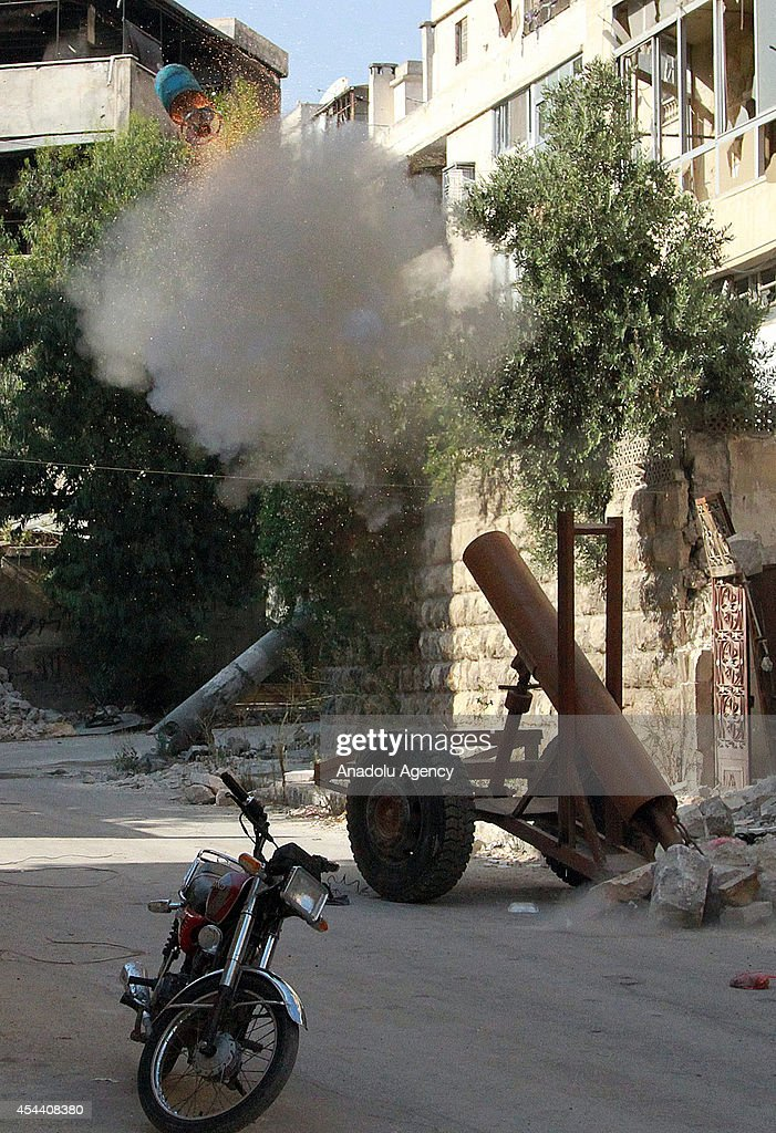 Islamic Front members bomb with propane cylinders against Aleppo's Seif al-Dowla during operation targeting the regime forces' building used in cantonment in Aleppo, Syria on August 30, 2014.