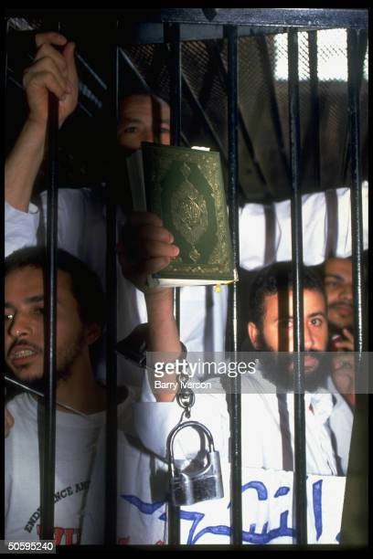 Islamic fundamentalist members of Gamaat Islamiya behind bars waving Koran during mil court trial charged w attacks on tourists plot to overthrow govt