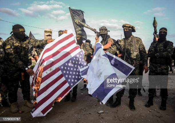 Islamic Jihad activists seen burning the Israel and United States of America flags during an Anti-Israel and USA military parade in the south of the...