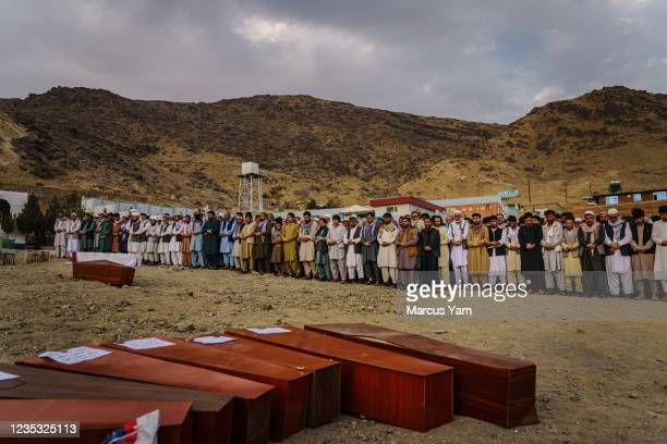 Islamic prayers are recited for the dead before they could be laid into the ground to be buried, as around 200 people attend a mass funeral for the...