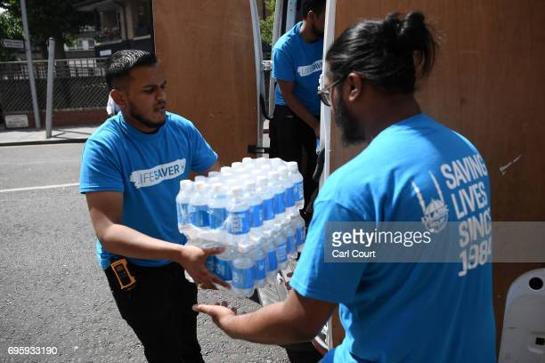 Islamic Relief charity workers arrive with bottled water near the 24 storey residential Grenfell Tower block in Latimer Road West London on June 14...