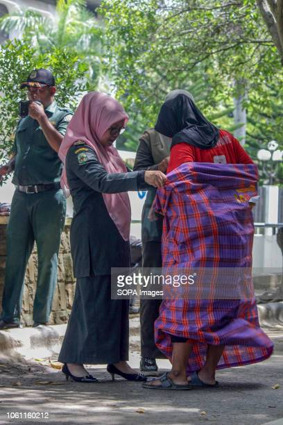 LHOKSEUMAWE ACEH INDONESIA Islamic Sharia Police Officer is seen tying a sarong to a woman who violated the Islamic Sharia law by force in the city...
