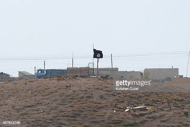 Islamic State black flag flies neasr the Syrian town of Kobani October 27 2014 as seen from the TurkishSyrian border near the southeastern town of...