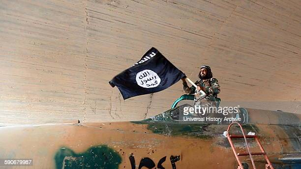 Islamic State fighter waving a flag while standing on captured government fighter jet in Raqqa, Syria, 2015.
