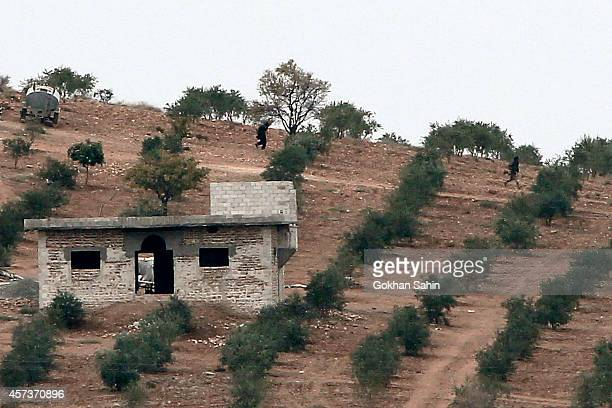 Islamic State militants walk down a hill in the outskirts of Syrian city of Kobani, as seen from the outskirts of Suruc, on the Turkey-Syria border,...
