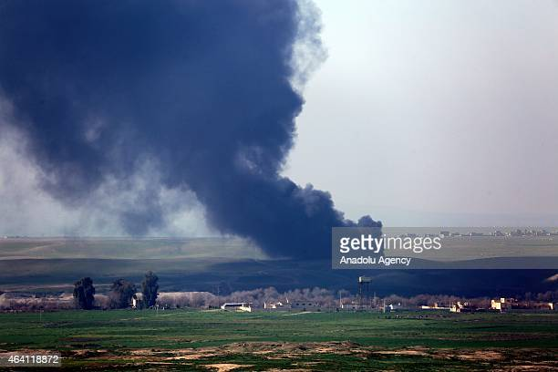 Islamic State of Iraq and the Levant members burn tires to lower the field of view as they running away after the nightlong clashes with the...