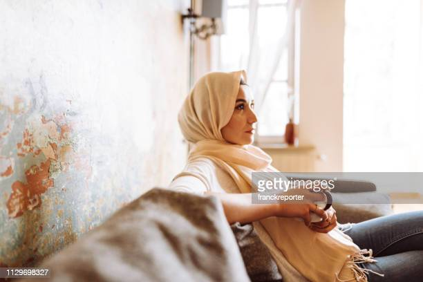 islamic woman with veil on the sofa - hot arab women stock photos and pictures
