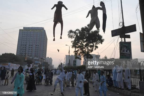Islamist students throw footwear toward effigies representing Asia Bibi a Pakistani Christian woman who was recently released after spending eight...