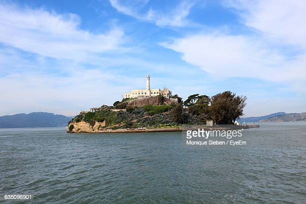 island amid calm sea against the sky - alcatraz stock photos and pictures