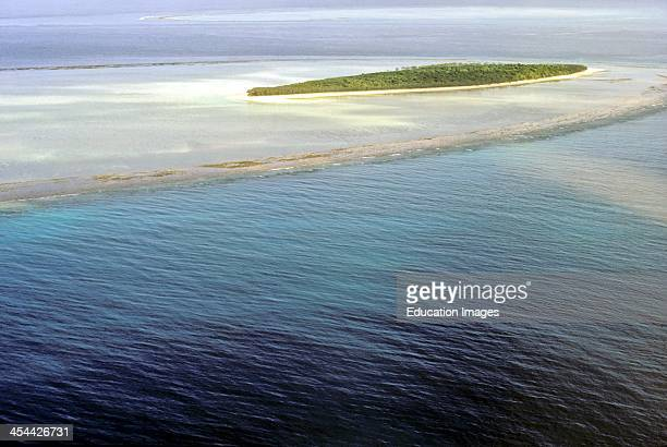 Island in the Capricorn group in a coral reef Note reef flat and coral cay island of coral sand Aerial Great Barrier Reef Australia