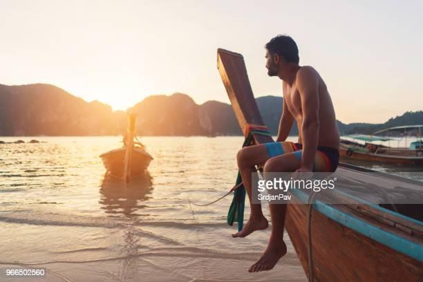 insel unter der sonne - asiatisches langboot stock-fotos und bilder