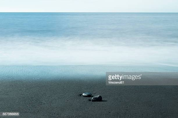 Island, two pebbles lying on dark sandy beach at waterfront