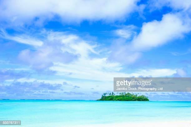 Island under blue sky in tropical ocean