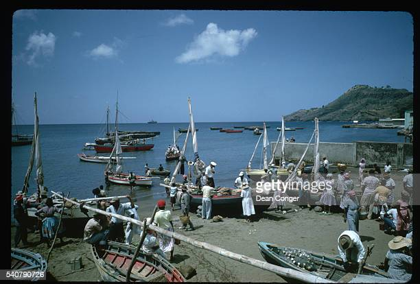 Island women buy fish from fishermen in their boats along the beach. Kingstown, St. Vincent Island.
