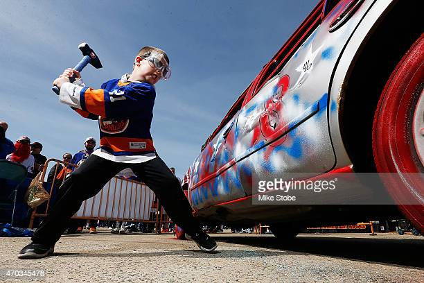 Islander fans participate in hitting the Smash Car prior to the game between the New York Islanders and the Washington Capitals the during Game Three...