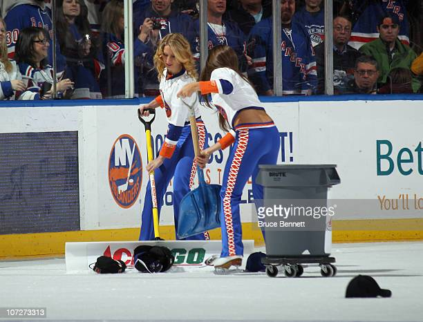 Islander ice girls clean up the hats from the ice following a hat trick by Marian Gaborik of the New York Rangers against the New York Islanders at...