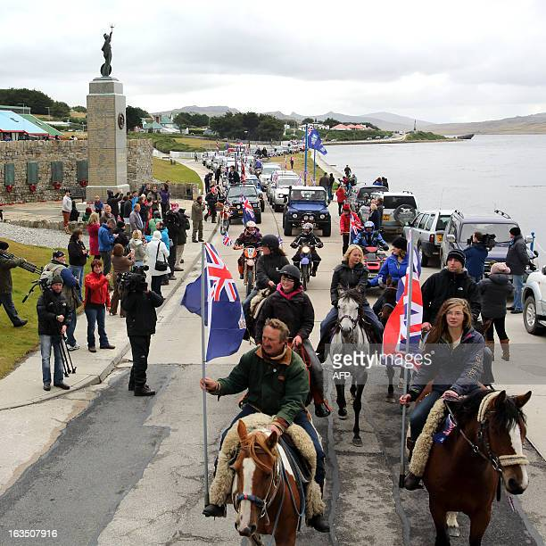 Islanders taking part in the 'Proud to be British' parade pass by the 1982 memorial along Ross Road in Port Stanley Falkland Islands on March 10 2013...