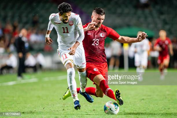 Ismaeel Hasan of Bahrain fights for the ball with Andrew James Russell of Hong Kong during the FIFA World Cup Asian Qualifier 2nd Round match between...