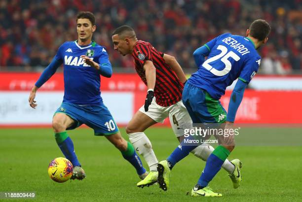 Ismael Bennacer of AC Milan competes for the ball with Filip Djuricic and Domenico Berardi of US Sassuolo during the Serie A match between AC Milan...