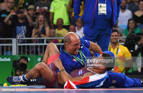 Ismael Borrero Molina of Cuba celebrates with his team after defeating Shinobu Ota of Japan in the Men's GrecoRoman 59 kg Gold Medal match on Day 9...