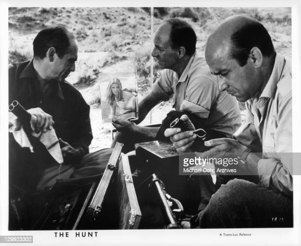 Ismael Merlo looks at the photo of a woman Alfredo Mayo is holding in a scene from the film 'The Hunt' 1967