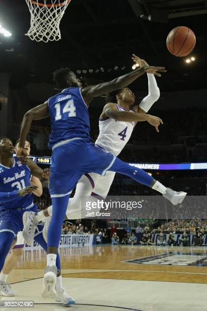 Ismael Sanogo of the Seton Hall Pirates defends the basket against Devonte' Graham of the Kansas Jayhawks in the first half during the second round...