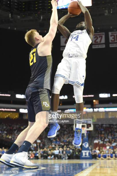 Ismael Sanogo of the Seton Hall Pirates takes a jump shot over Harry Froling of the Marquette Golden Eagles during a college basketball game at the...