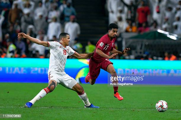 Ismail Ahmed Mohamed of the UAE challenges Akram Hassan Afif of Qatar during the AFC Asian Cup semi final match between Qatar and United Arab...