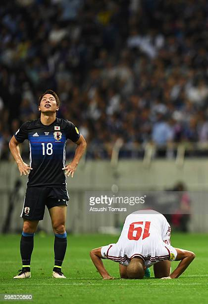 Ismail Ahmed of the United Arab Emirates celebrates his team's 2-1 win while Takuma Asano of Japan shows dejection after the 2018 FIFA World Cup...