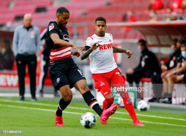Ismail Jakobs of FC Cologne battles for possession with Mathias Jorgensen of Fortuna Duesseldorf during the Bundesliga match between 1. FC Koeln and...