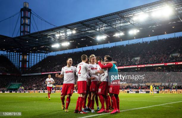 Ismail Jakobs of FC Koln celebrates with his teammates after scoring his sides fourth goal during the Bundesliga match between 1. FC Koeln and...