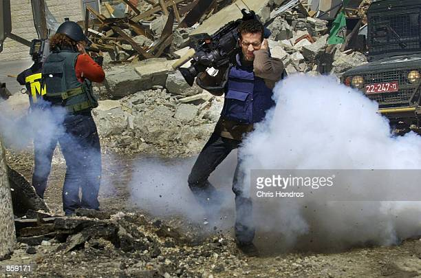Ismail Khader a video cameraman for the Reuters News agency recoils as a concussion grenade explodes at his feet April 5 2002 in the West Bank city...