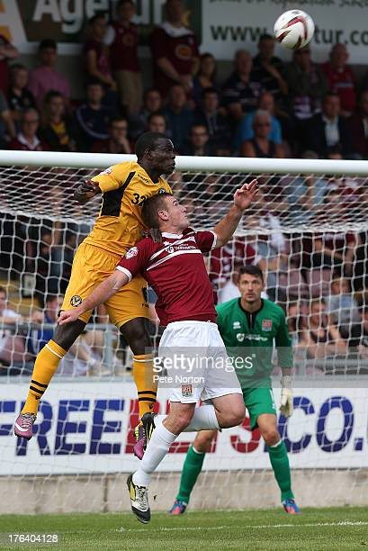 Ismail Yakubu of Newport County AFC heads the ball under pressure from Lee Collins of Northampton Town during the Sky Bet League Two match between...