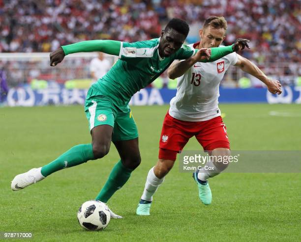 Ismaila Sarr of Senegal is challenged by Maciej Rybus of Poland during the 2018 FIFA World Cup Russia group H match between Poland and Senegal at...