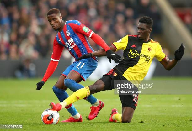 Ismaila Sarr of Watford and Wilfried Zaha of Crystal Palace battle for the ball during the Premier League match between Crystal Palace and Watford FC...
