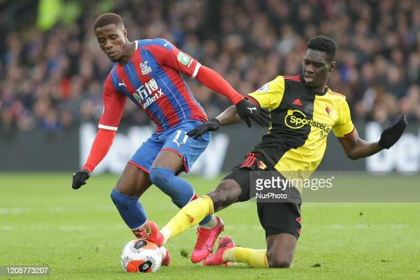 Ismaila Sarr of Watford and Wilfried Zaha of Crystal Palace battling for possession during the Premier League match between Crystal Palace and...