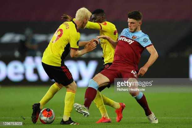 Ismaila Sarr of Watford and Will Hughes of Watford compete for the ball with Declan Rice of West Ham United during the Premier League match between...