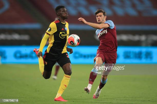 Ismaila Sarr of Watford battles for possession with Aaron Cresswell of West Ham United during the Premier League match between West Ham United and...
