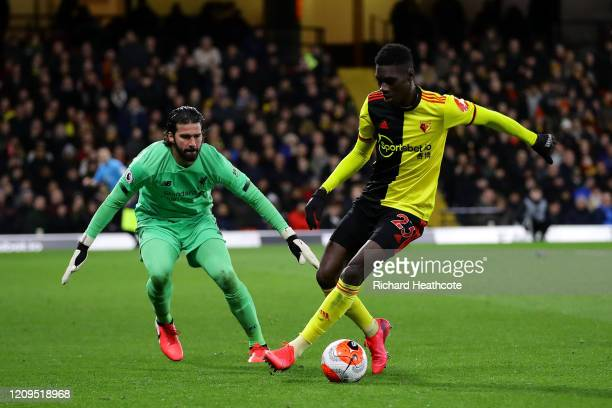 Ismaila Sarr of Watford goes around Alisson Becker of Liverpool to score his team's second goal during the Premier League match between Watford FC...