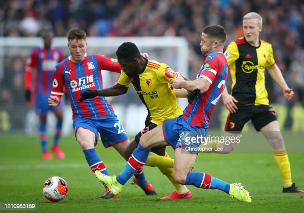 Ismaila Sarr of Watford is tackled by Gary Cahill of Crystal Palace during the Premier League match between Crystal Palace and Watford FC at Selhurst...