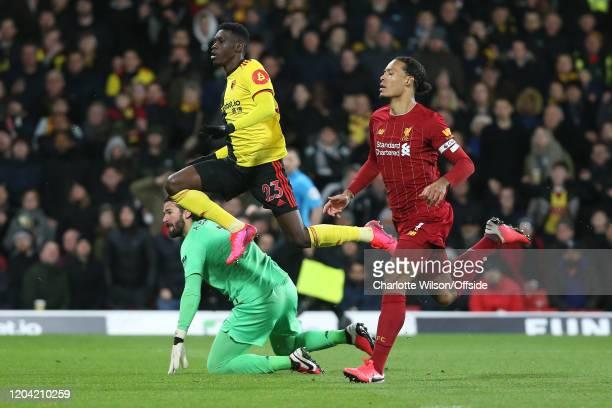 Ismaila Sarr of Watford jumps over a dejected Liverpool goalkeeper Alisson Becker after scoring their 2nd goal Virgil van Dijk of Liverpool trails...