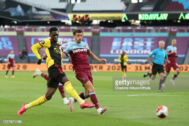 Ismaila Sarr of Watford shoots past Aaron Cresswell of West Ham during the Premier League match between West Ham United and Watford FC at London...