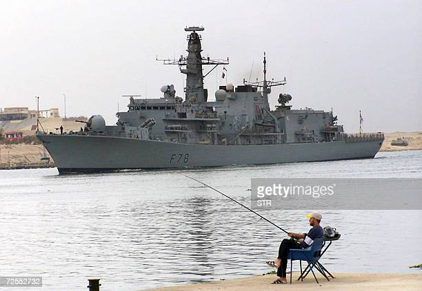 An Egyptian man catches fish as the British destroyer HMS Kent passes through the Suez Canal off the Egyptian port of Ismailia 100 kms northeast of...