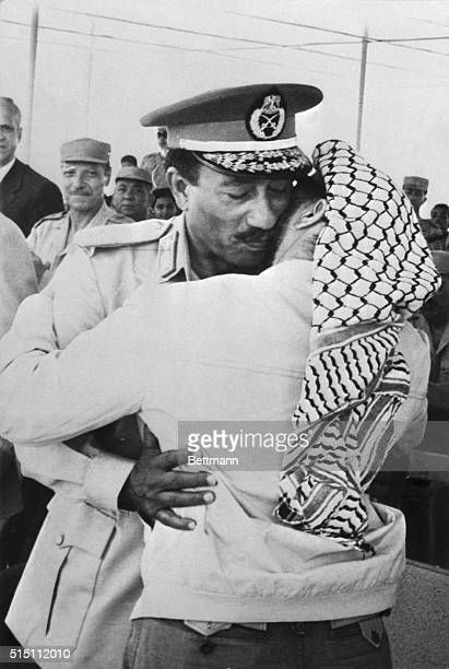 6/5/1974 Ismailia President Anwar Sadat embraces Palestine Liberation Organization leader Yasser Arafat during military parade held here 6/5 on the...