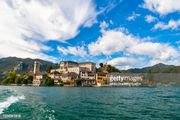 isola san giulio inside orta's lake, piemonte, italy, from water surface with blue sky. - stresa stock pictures, royalty-free photos & images