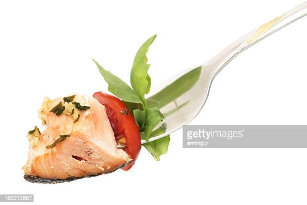Isolated background of salmon, rucola and tomato on fork