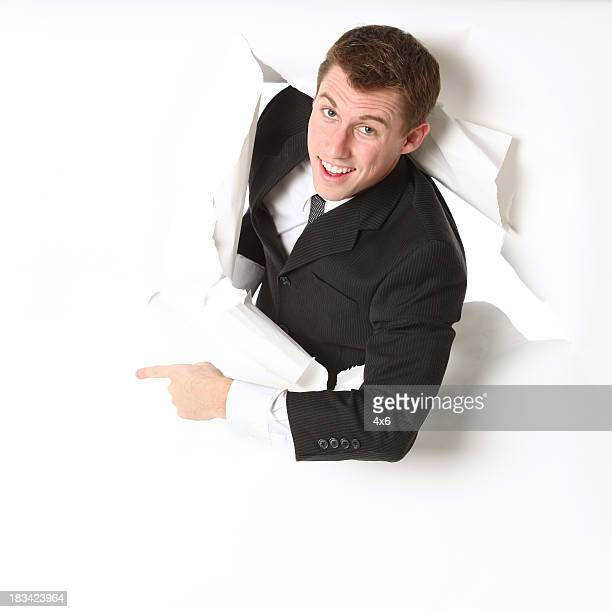 Isolated businessman emerging through a hole and pointing