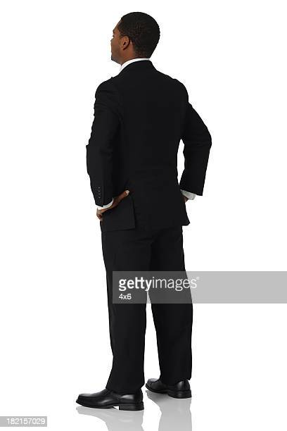 Isolated businessman hands on hips rear view