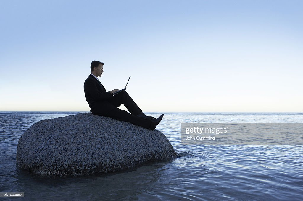 Isolated Businessman Sitting on a Rock in the Sea and Using a Laptop Computer : Stock Photo